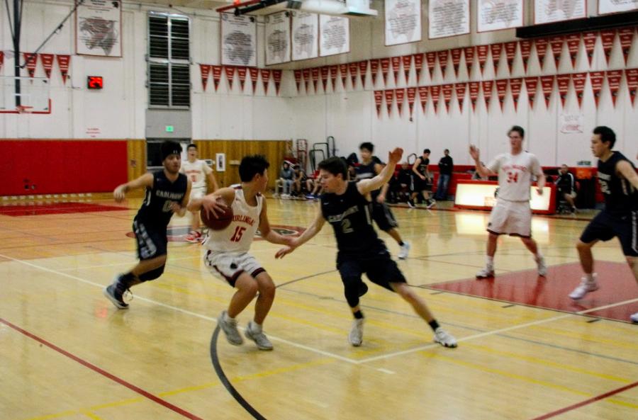 Freshman guard Jacob Yamigishi steps back to avoid the Carlmont defender.