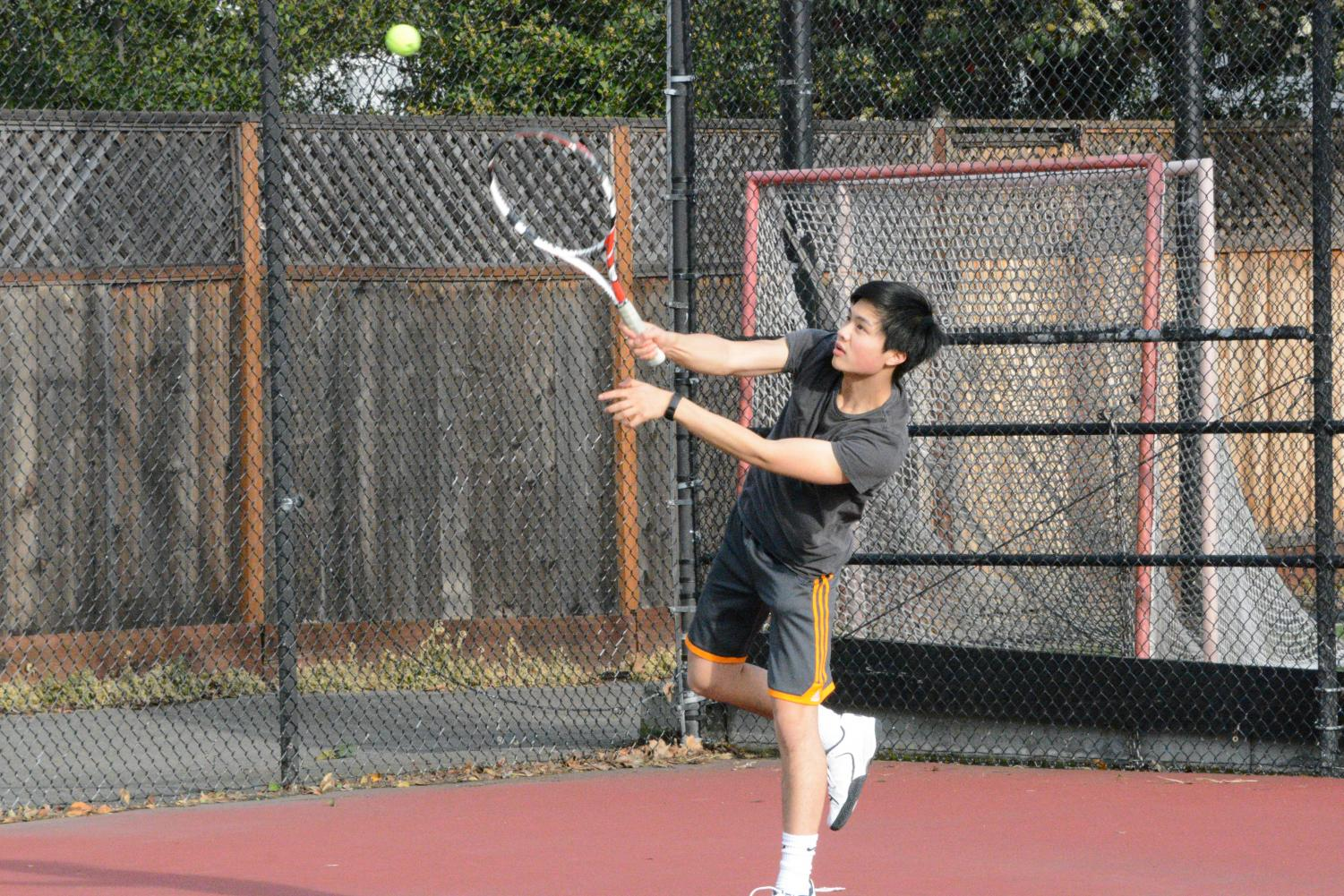 Junior Justin Hee serves in a home game against the San Mateo Bearcats.