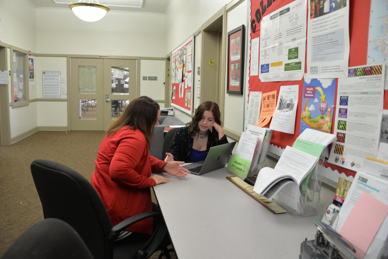 Senior Dana Rienks Alfaro converses with academic counselor Carla Renzi about committing to a college. The academic counseling department will continue to be a central college advice resource for AVID and non-AVID students next year.