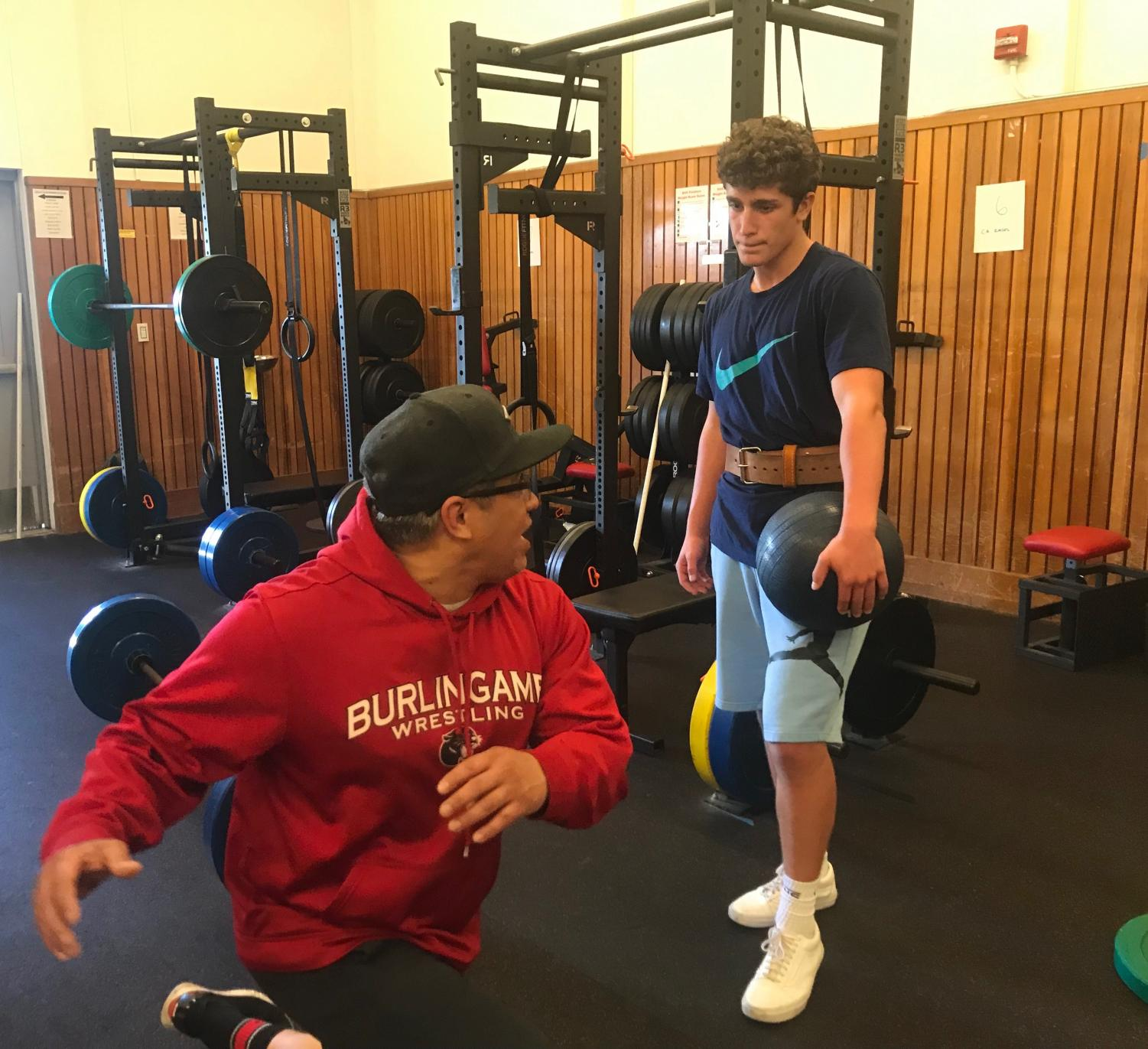 Núñez explains an exercise to sophomore Isaac Frankel during football's weight training.