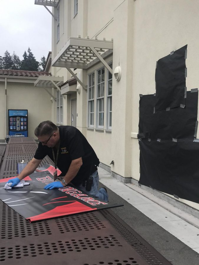 School Plant Operator Employee Victor Delaplaine removes the swastika from a banner.