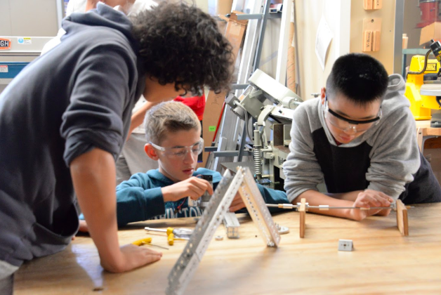 Finn Sheehy (middle) assembles parts.