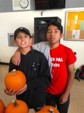 Two juniors pose for the camera after choosing their ideal pumpkin.
