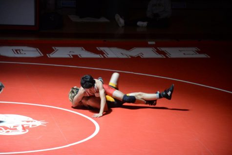 Varsity wrestler Kent Liao sprawls on top of his opponent.