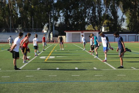 Burlingame football players stretch during their warm up on Oct. 15.