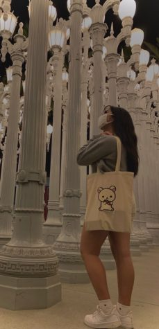Arriana Cruz poses with a custom-made bag that she painted a Japanese bear named Korilakkuma on.