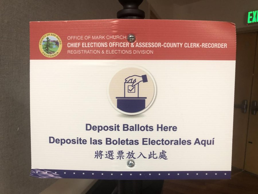 A sign at San Carlos Library's voting center prompts voters to drop their ballots in the correct box.