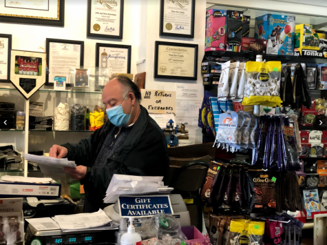 John Kevranian, owner of Nuts for Candy, shuffles through papers waiting anxiously for customers.