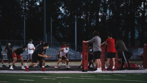 Burlingame's varsity football players follow COVID-19 precautions while practicing drills on the football field.