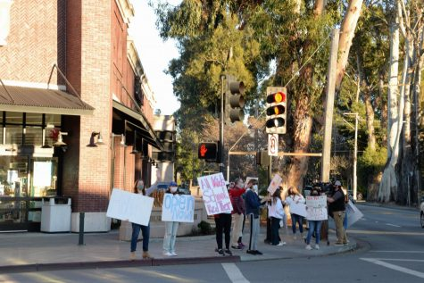 Parents stand on the corner of El Camino Real and Burlingame Avenue, holding signs to advocate for the reopening of high schools.
