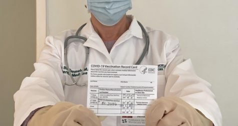 Hiva Bastanmehr, a physician, holding her COVID-19 vaccination record card to show proof of vaccination against the virus.