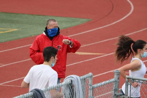 Coach Steve O'Brien checks his stopwatch as senior Chris Percia passes by.