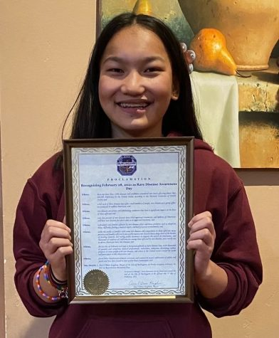 Junior Rachel Burdick proudly presents the official proclamation from the City of Burlingame recognizing the last day of February as Rare Disease Day.