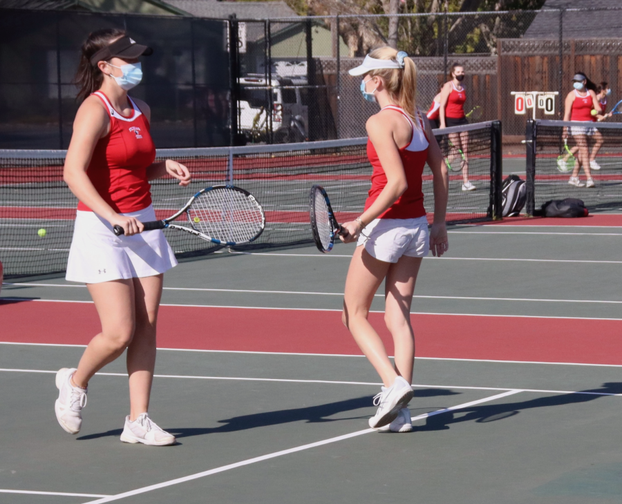 Juniors Annika Ganguly (left) and Molly Wachhorst (right) high five with rackets during their doubles match.