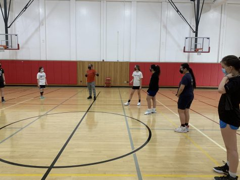 The girl's basketball team prepares for drills in the small gym.