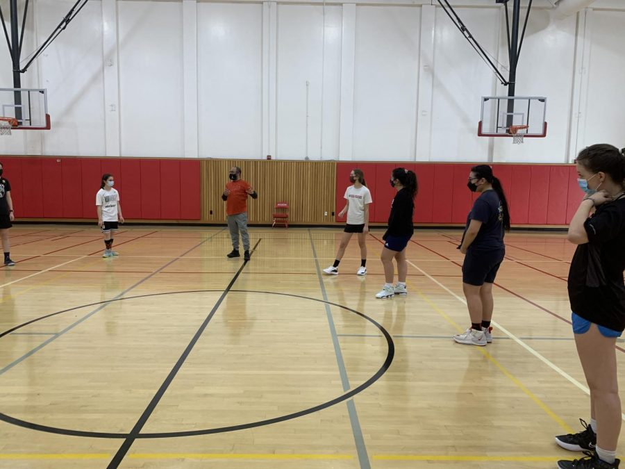 The+girl%E2%80%99s+basketball+team+prepares+for+drills+in+the+small+gym.