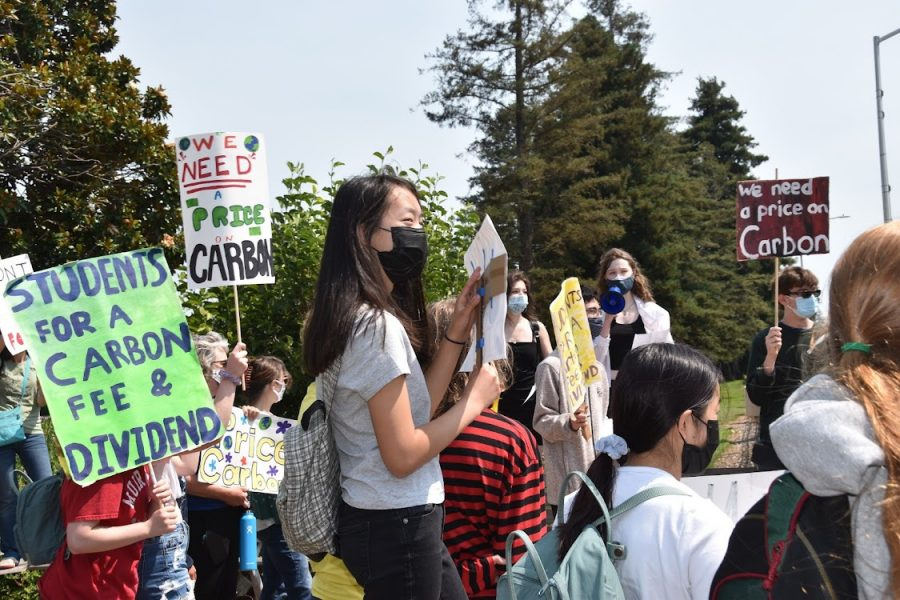 """Attendees of the """"Students for a Carbon Fee & Dividend Rally"""" raise colorful signs on the corner of East Fifth Avenue and El Camino Real on Saturday."""