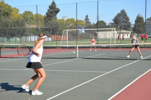 Sophomore Lily Grenier and juniors Malia Schmidt and Spencer Dobos play doubles against each other at practice on Thursday, Aug. 26.